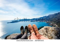 Couples legs in shoes together on the mountains and sea background