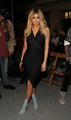 Kylie Jenner wears a black striped knee-length dress with Dior glove boots