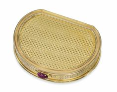 AN 18 CARAT GOLD AND RUBY COMPACT, BY CARTIER  Of saddle form, with engine turned hatched decoration throughout, to stepped rose gold borders, the cabochon ruby thumb piece opening the hinged cover to reveal a bevelled mirror and powder compartment, London hallmarks for 18 carat gold, 1956