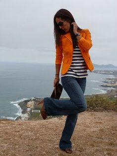 Women wearing a bright blazer with neutral outfit. Dark wash boot cut jeans and striped shirt.