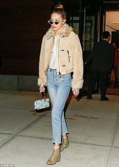 Cosy coat! The Victoria's Secret model donned a beige winter jacket with fuzzy neckline an...