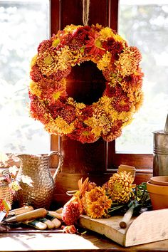 Late-blooming chrysanthemums are the perfect way to bring the beauty of fall into your home. This stunning autumn wreath boasts a collection of autumnal-hued golden, maroon, and burnt sienna mums. #falldecor #fallideas #wreathideas #fallwreath #wreath #bhg
