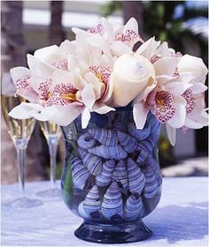 Elegant beach theme centerpiece with seashells and flowers. Perfect for beach wedding or event!