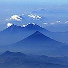 "Four Volcanoes in Guatemala This photo of volcanoes in Guatemala was taken from NASA's C-20A aircraft during a four-week Earth science radar imaging mission deployment over Central and South America. The conical volcano in the center is ""Volcan de Agua."" The two volcanoes behind it are, right to left, ""Volcan de Fuego"" and ""Acatenango."" ""Volcan de Pacaya"" is in the foreground."
