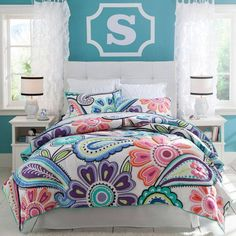 Colorful with a bold initial above the bed.