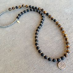 Unisex mala, with 54 beads, made with ebony and genuine tiger´s eye beads. It wraps as a bracelet, (stringed on thick hi-tec elastic) and doubles as a necklace! With an Om pendant. (You may ask to hav