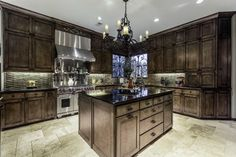 Traditional kitchen with dark wood cabinets, rustic wrought iron chandelier and honed travertine floors