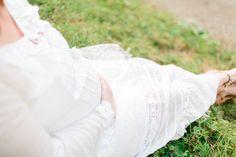 Une fture maman en robe longue blanche avec de la dentelle et des fleurs