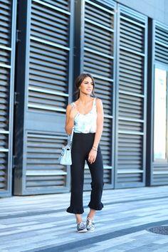 Camila Coelho wearing a printed floral sleeveless top with a black pantacourt, metallic oxfords and a light blue purse. Look do dia com regata estampada com pantacourt preta, sapatos oxford metalizado e uma bolsa azul clara.