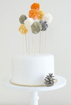 Brides.com: Wedding-Worthy One-Tier Cakes. A White Wedding Cake Topped with Colored Pom Poms. Go full-on festive by popping some colorful pom poms atop your one-tier wedding cake. A tiny silver pine cone at the base adds a bit of rustic charm to the whimsical look.  See more round wedding cakes.
