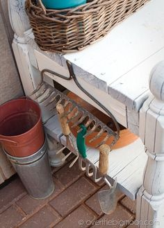Old rake used for storing gardening tools on potting bench. Great idea!