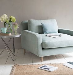 Loaf's comfy and cosy Snuggalump love seat in a light duck egg linen with a vase of fresh blooms