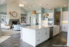 kitchen and family room / great room… simple, clean, fresh. Especially in love with that huge island and the beautiful distressed grey wood floor. kitchen and family room / great… New Kitchen, Kitchen Decor, Kitchen Living, Kitchen Wood, Living Room And Kitchen Together, Kitchen White, Kitchen Colors, Room Kitchen, Kitchen Ideas