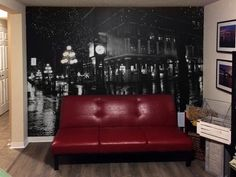 Looking for an easy solution to transform the look of your walls? Try this wallpaper mural! The red couch and the black and white cityscape mural create a nice contrast in the living room!