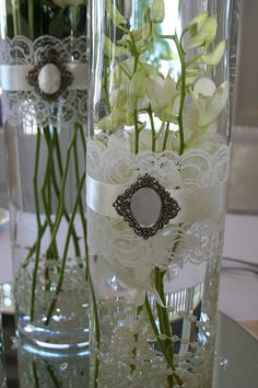Glass cylinder centerpieces with lace.