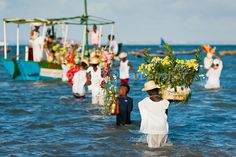 Candomblé devotees carry flower baskets onto a boat during the ritual ceremony in honor to Yemanjá, the goddess of the sea.