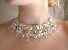 This necklace is a take of on my rhinestone illusion necklaces, but in a collar-like style. I used ivory flat back pearls and clear AB (rainbow coated) rhinestones to create an elegant and dramatic effect. This style of necklace can be worn with a larger variety of ensembles as it sits higher up ...