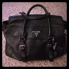 """Authentic Prada Vitello Daino Satchel This gorgeous vintage bag is in very good condition! Inside is slightly scuffed from use but can be cleaned. The shoulder strap is missing but it looks great as a satchel. Top closes with magnetic flap. 1 zip and 2 open pockets on inside. Still has luggage tag. Silver hardware with all Prada markings, Prada embroidered lining, Prado logo tab on inside, and Prada engraved leather tag all intact. Pebbled black leather. 9"""" deep, 9.5"""" wide, About 13.5"""" long…"""