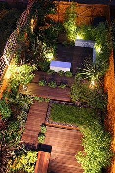 Entertaining Night Garden. The enclosed feel of this small urban garden has been transformed using an asymmetrical layout with architectural planting to keep the eye within the garden space, and multiple surfaces to provide variety. A small lawn is packed with spring-flowering Crocus to give an extra burst of colour.