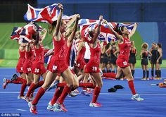 Team GB players wave Union Jack flags on the pitch after defeating the Dutch on penalties