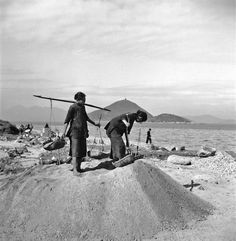 Women laborers shifting building sand with Victoria Harbour  in the background, Hong Kong Island, 1946-47