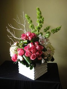 18 roses, hydrangea, bells of Ireland, cymbidium orchids, sandblasted Manzanita, rolled leaves and filler.
