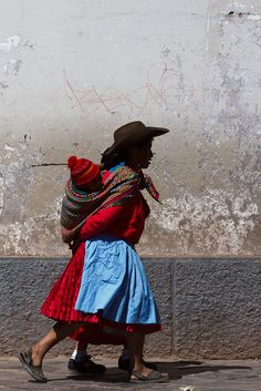 South America | Portrait of a Aymara mother wearing traditional clothing and carrying her child, Peru | Kim