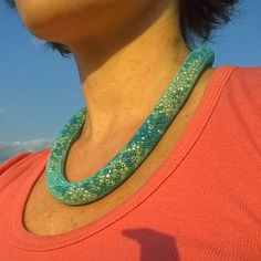 nylon mesh necklace in gold and turquoise  * turquoise nylon mesh tubing * filled with glass seed beads in gold and shades of blue and turquoise * mesh creates pixelated snake skin effect * silver tone magnetic tube clasp * about 19'' long * tube diameter about 9 mm