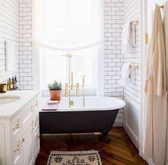 Black claw foot tub subway tile grey grout hard wood floors gold hardware
