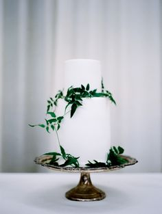 elegant white cake adorned with greenery | Photography: Czar Goss