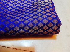 This beautiful blue brocade fabric has small woven motifs in gold. This combination of blue and gold gives a very royal and rich look.This