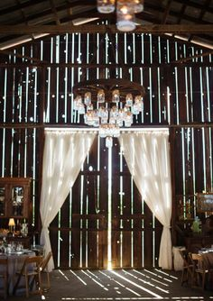Gorgeous farmhouse entryway with white curtains and a rustic chandelier #weddingdecor