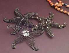 Here is a pile of 4-5 inch starfish all worked in steel. One has goldplate over brass beads, and the other showcases white beach glass.