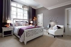 A Contemporary Master Bedroom In Dove Gray And Purple. This Suite Includes  Both A Walk In Closet And A Master Bathroom. A Small Seating Area Rests  Between ...