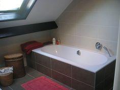 Bad onder schuin dak afgewerkt met tegels. Inbouwkraanwerk van Hansgrohe met Exafill (vulling via overloop).