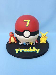 """Pokémon ball"" cake with Pikachu and Charmander edible cake toppers."