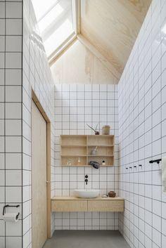 Lavatório em casa de estilo escandinado, com bancada em madeira e cuba de apoio, azulejos com rejunte contrastando linda luz que vem do telhado.