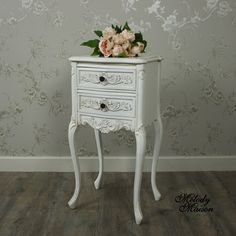 Louis XV Range - Ivory Ornate Bedside Table A beautifully ornate 2 drawer bedside table in a French style With intricate detailing in a Fleur de Lys design and round brass drawer knobs Painted in an ivory colour with a distressed finish that gives an aged look See other items in this range