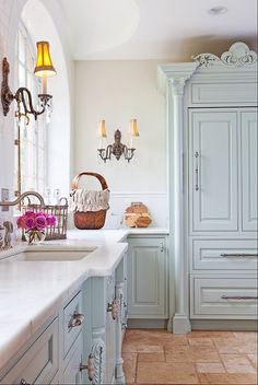 A soft color palette, furniture-style cabinetry, vintage accessories and a timeless white marble countertop are key elements of French country-kitchen style.