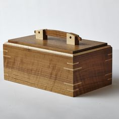 Curly walnut and maple box with splined-miter joints and inset lid with pinned bracket handle.