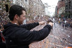 San Francisco Giants catcher Buster Posey acknowledges fans atop of a double deck bus during the San Francisco Giants World Series victory parade along Market Street in San Francisco, Calif., on Friday, Oct. 31, 2014. (Ray Chavez/Bay Area News Group)