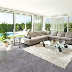 A contemporary lounge with large windows featuring Alaska Grey marble effect thin porcelain floor tiles with antibacterial nanotechnology Large Floor Tiles, Marble Floor, Tile Floor, Bilbao, Contemporary Lounge, White Sofas, Marble Effect, Outdoor Furniture Sets, Outdoor Decor