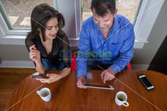 Overhead view of working colleagues during a coffee break, a man and a woman sitting at the breakfast table working with PC tablet and…