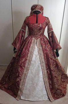 Abito in damascato color borgogna, con sottogonna bianca. L'abito è impreziosito da passamanerie ed è completo con un copricapo alla francese. Costo £120