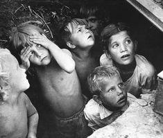 Children watch as their neighborhood is bombed in Minsk, Belorussia. The bombing was part of Operation Barbarossa. June, 1941