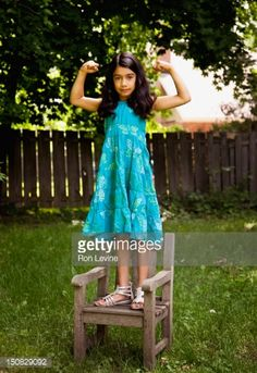 Stock Photo : Young girl flexing muscles while standing on chair