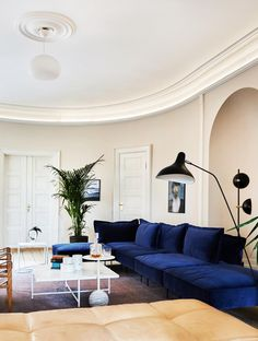 Extravagant living room with a lovely blue velvet sofa and marble tables.