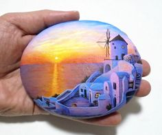 Hand painted rock Landscape with the beautiful sunset in the Greek Island of Santorini ! A great handmade painted stone made by me!  Is painted on a smooth sea stone which i have collected from a beach on a Greek island. Is painted with fine art quality acrylic colors and very small brushes for the detail , is signed on the back and covert with strong acrylic stone varnish for protection.  Dimensions approximately : Height : 8.5 cm ( 3.3 in ) Width : 11 cm ( 4.3 in )  Your art works will…
