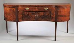 "A Southern Federal Inlaid Mahogany Serpentine Sideboard in the Hepplewhite Taste, c. 1800, the top with banded and line inlay, long drawer over doors, flanked by cupboards, raised on square tapered legs with banded cuffs, height 37 1/2 in., width 76 in., depth 30 in.   Note: Drawer with label ""property of Mr. E.G. Dixon loaned to Mrs.? 4/May 3rd 1905"". Another label inside state: ""Maude R. Coss/Dining room furniture...belongs to Alyre Mr. Miller of Tulsa, Okla., Sept 18, 1924""."