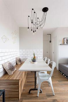 Decoração de apartamento que mistura estilos, mas com predomínio do estilo escandinavo, com uma base branca e leve. Na sala de jantar mesa de jantar branca retangular, cadeira branca e banco de madeira.